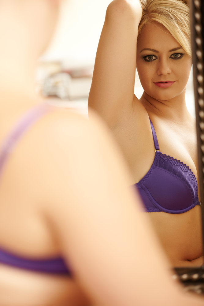 Woman in front of mirror in bra